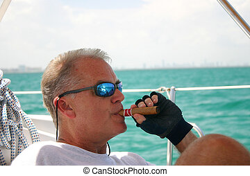 Middle aged Man on Sailboat - Middle-aged man smoking cigar...