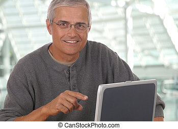 Middle Aged Man Pointing at Laptop - Middle aged man sitting...