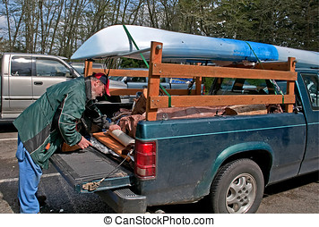 Middle Aged Man Preparing Truck for Camping and Kayak Trip