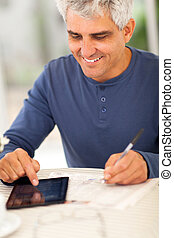 middle aged man reading newspaper and making notes