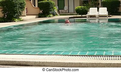 Middle-aged man relaxing and slowly swims in hotel swimming pool.