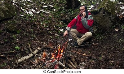 Middle-aged man sits by the fire in the forest alone and...