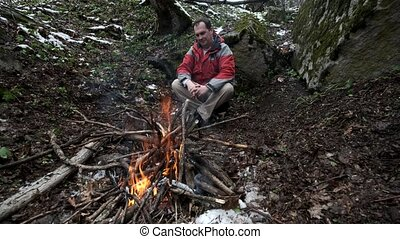 Middle-aged man sits by the fire in the forest alone