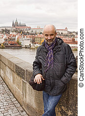 Middle-aged man smiling on the Charles Bridge