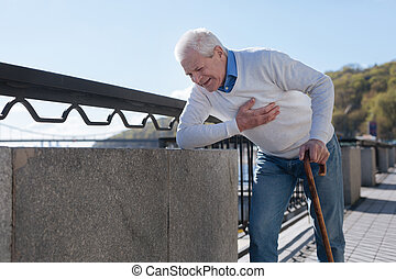 Middle aged man suffering from pain in the street