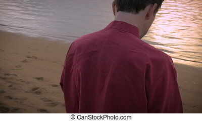 Middle aged man swiping and checking his cell phone while on the beach at sunset