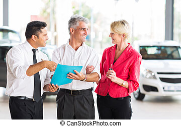 middle aged man talking to wife before buying a new car at...