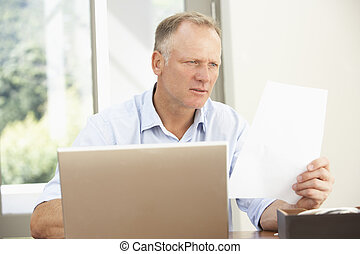 Middle Aged Man Using Laptop At Home