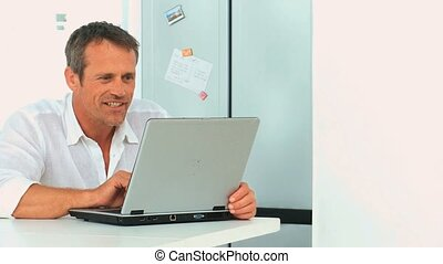 Middle aged man winning something on his laptop in the...