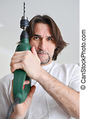 middle-aged man with a drill in  hands of