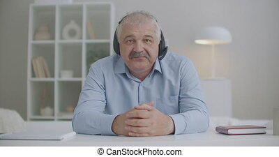 middle-aged man with headphones on head is nodding and looking at camera, video calling and online chatting concept, view from web camera of laptop