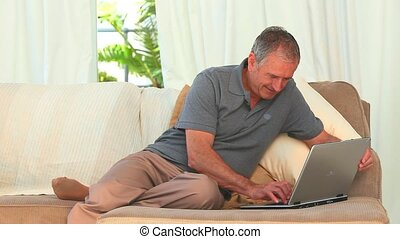 Middle aged man working on his laptop at home
