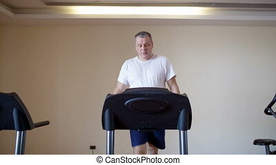 Middle-aged man working out on a treadmill - Wide shot of...