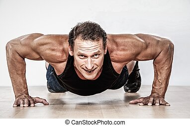 Middle-aged muscular man doing push-up