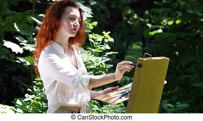 Middle aged redhead woman with an easel in the forest - ...