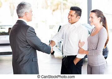 middle aged salesman handshaking with young couple