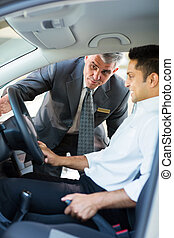 middle aged salesman showing new car interior to customer