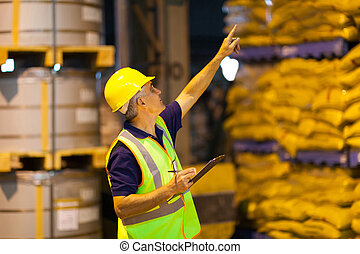 shipping company worker counting pallets - middle aged ...
