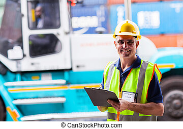 middle aged shipping worker standing in front of big forklift