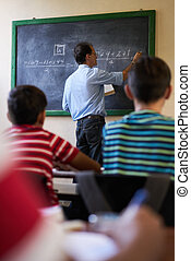 Middle Aged Teacher At Blackboard Giving Class Of Math