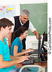 middle aged teacher helping students with computer