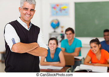 middle aged teacher standing in front of the class