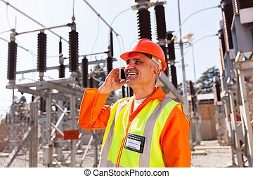middle aged technician talking on cell phone in substation