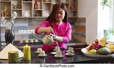 Middle aged Vietnamese woman prepares traditional Vietnamese tea at the bar of a cafe