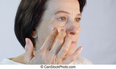 Middle aged woman applying cream on face - Middle aged woman...