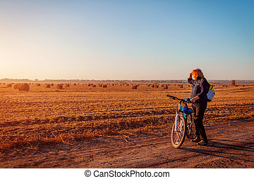Middle-aged woman bicyclist riding in autumn field at sunset. Senior sportswoman admiring the view.