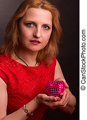 middle-aged woman blonde Studio portrait. Holding toy in shape of a heart.