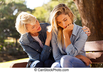 middle aged woman comforting her sad daughter