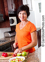 middle aged woman cooking in kitchen