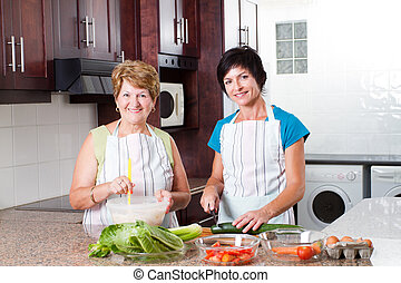 middle aged woman cooking with senior mother