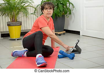 Middle-aged woman doing fitness exercises with tablet