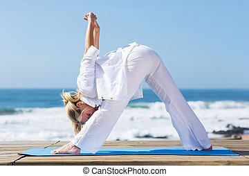 middle aged woman doing fitness stretching by the beach