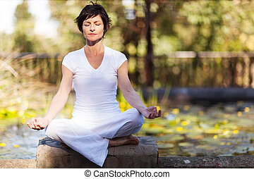 middle aged woman doing yoga meditation outdoors
