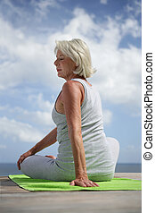 Middle-aged woman doing yoga outdoors