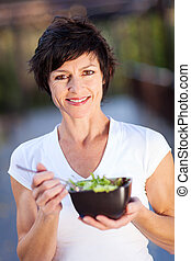 middle aged woman eating green salad