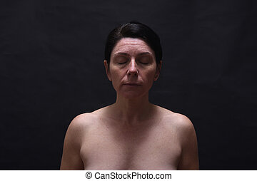 middle aged woman eyes closed on black background