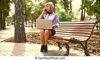 middle-aged woman full of fat sitting on park wind bench...