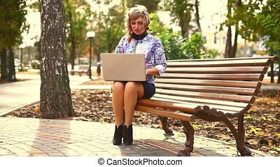 middle-aged woman full of fat sitting on park bench wind...