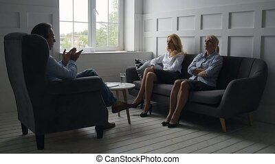 Professional advice. Serious women having a talk with psychiatrist while sitting on the sofa and being confident
