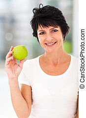 middle aged woman holding apple