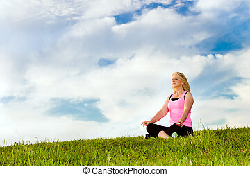 Middle-aged woman in her 40s meditating for exercise ...