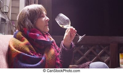 Middle aged woman in warm clothes sitting on the sofa