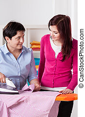 Middle-aged woman ironing shirt