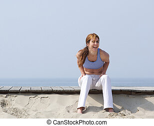 Middle aged woman laughing at the beach