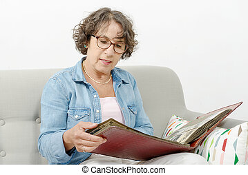 middle-aged woman looking at photo album