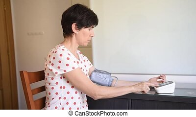 Middle-aged woman measuring her own blood pressure with an...